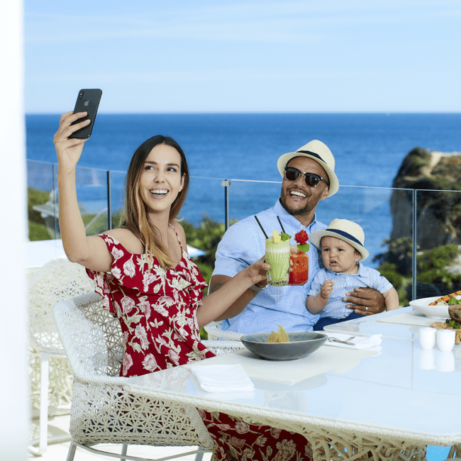 Family enjoying healthy breakfast and taking selfies
