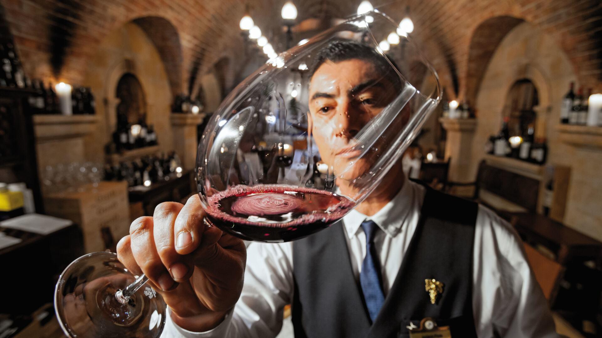 Sommelier sampling wine at Cave de Vinhos